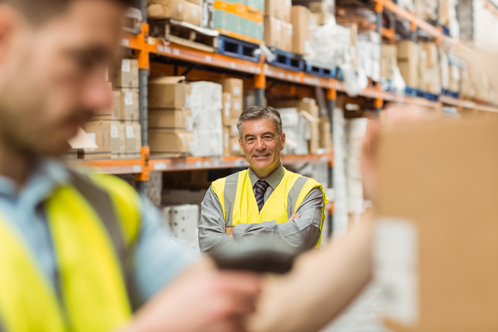 Warehouse worker scanning barcode on box in a large warehouse